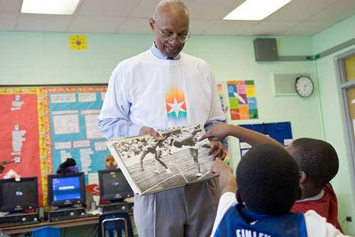 Black teacher showing kids a book